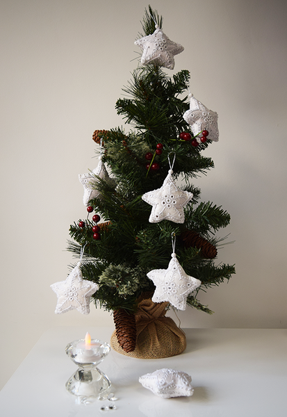 White star shaped Christmas decorations with white embroidery and mirror work on a tree