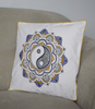 Embroidered yin-yang cushion cover in shades of ochre and lilac on a grey arm chair