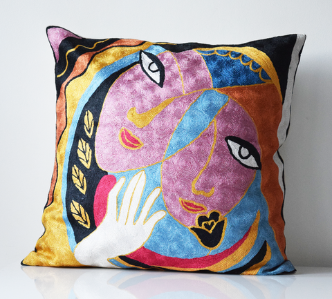 Abstract faces embroidered cushion cover in shades of pink, blue, black yellow orange and red