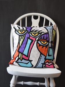 Abstract faces cushion with pink, yellow, orange and blue on a white background