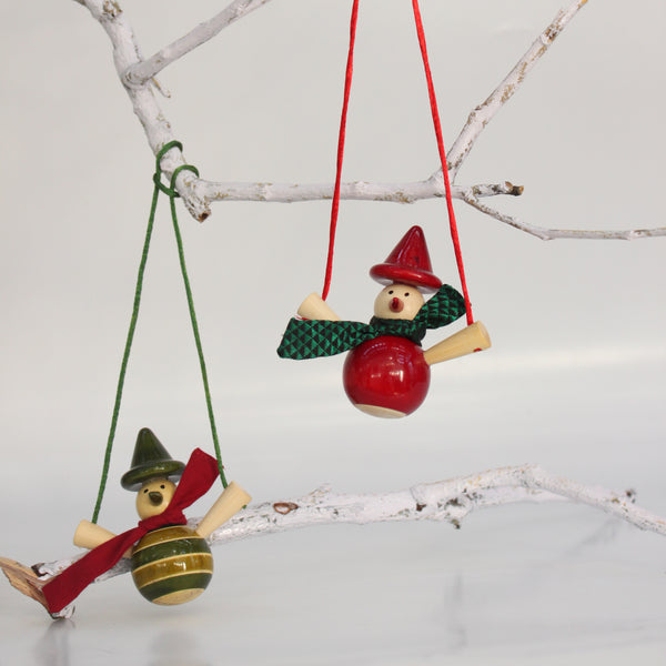 red and green wooden snowmen on a swing ornaments