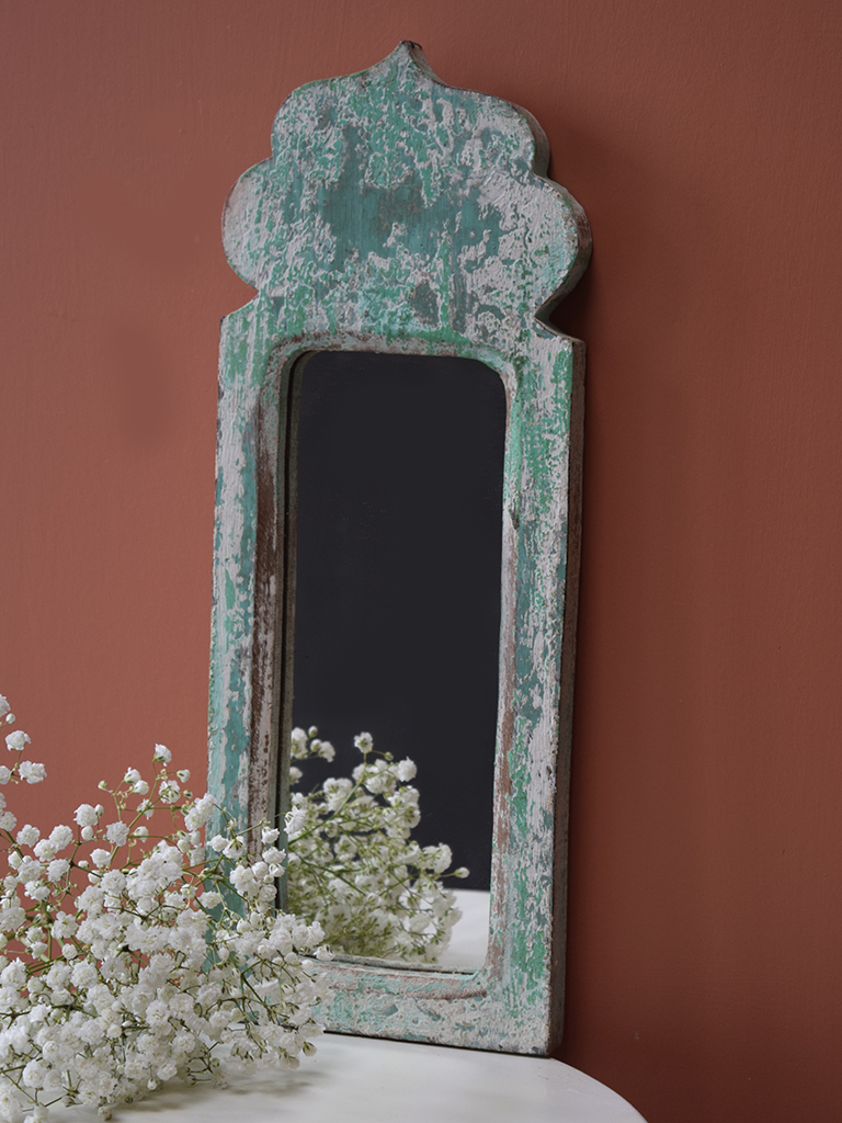 Green blue, distressed mirror against terracotta background