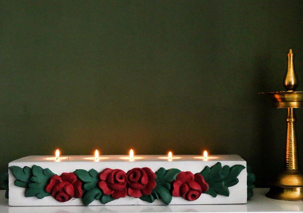 front view of grey tealight holder with burgundy roses against a green background, with a brass piece