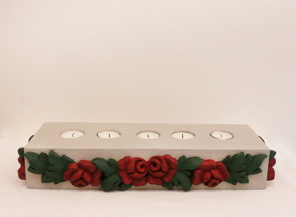 front view of grey candles stand with burgundy roses against a white background