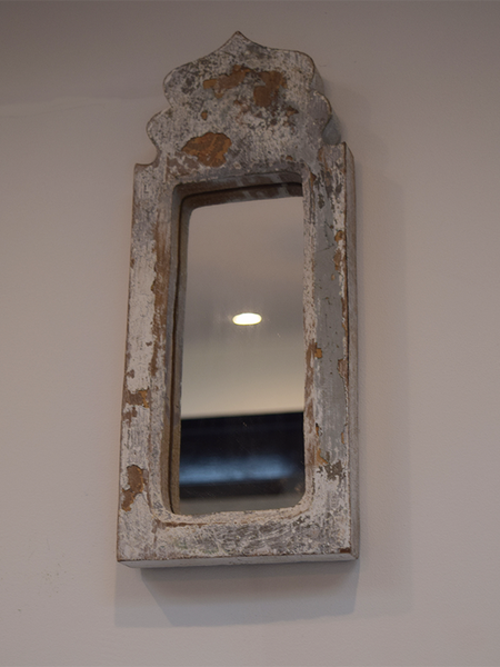 grey-white dome shaped distressed mirror against yellow background
