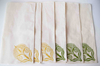 cream napkins with green and mustard floral block print.