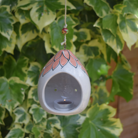 pictured in garden- terracotta colour on white floral pattern tealight holder, includes string and a terracotta coloured bead