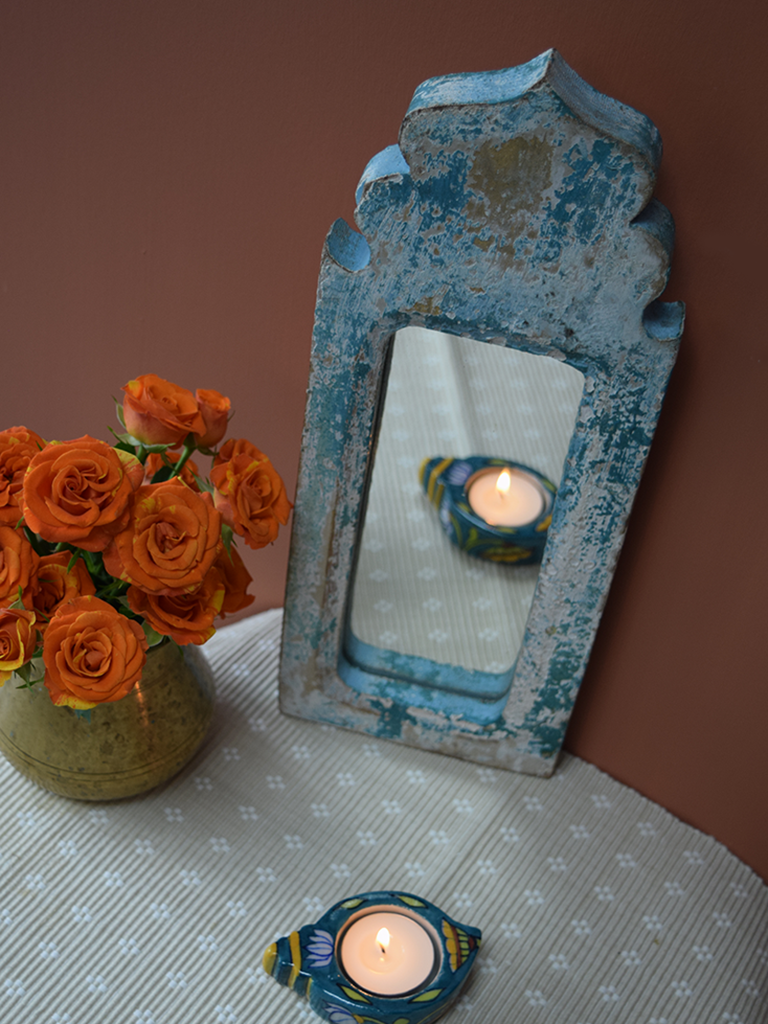 blue distressed dome shaped mirror against rust background