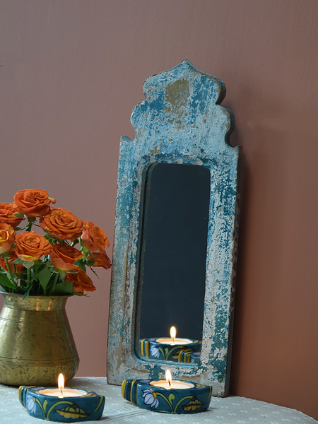 distressed blue dome mirror against terracotta background