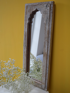 white minaret shaped distressed mirror against yellow background