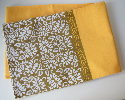 plain mustard table runner with floral brown block printed pattern on the ends