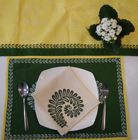 yellow table runner with green edging, green table mats and cream and green fern pattern napkin in a table setting