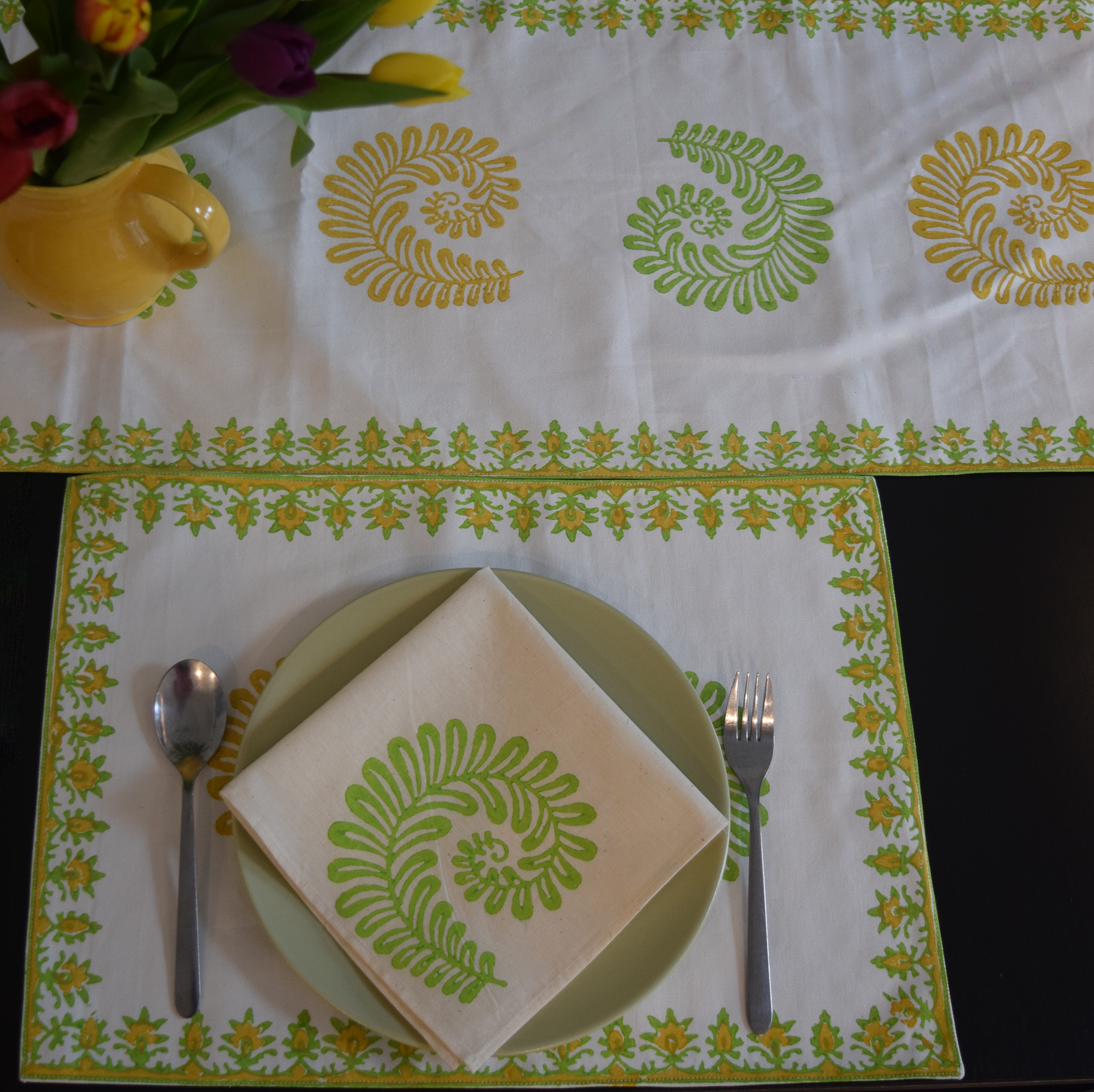 yellow and light green fern patterns on white background  in a table setting