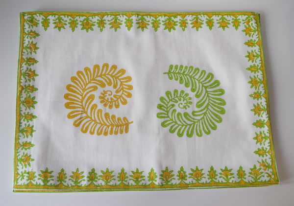 yellow and light green fern patterns on white background on a tablemat