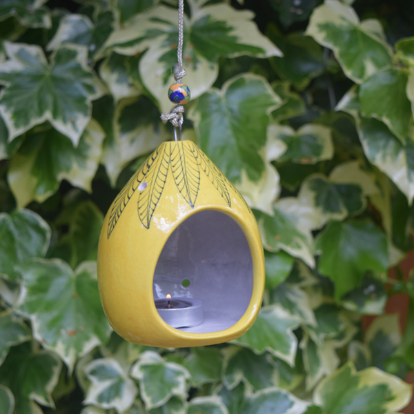 pictured in garden- yellow tealight holder with hand painted black leaf pattern, including a yellow and blue bead