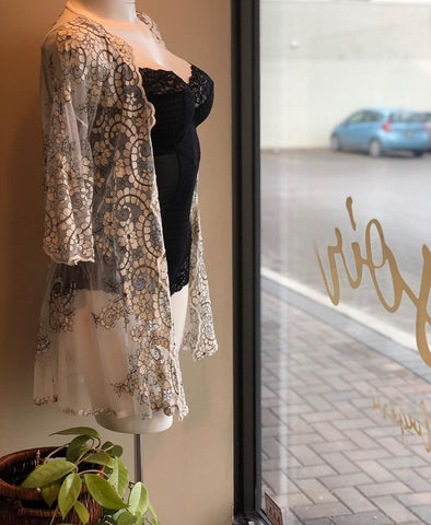 mannequin wearing a black bodysuit with a sheer embroidered robe in pear and black