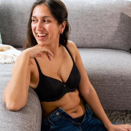 Pure Plus Bra Black front view lifestyle image, bra worn by model with unzipped jeans.