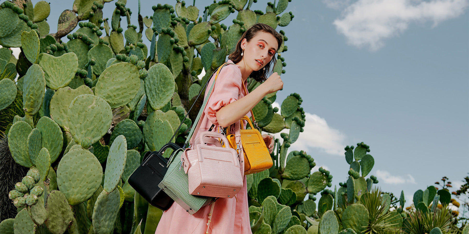 Juliette wearing a pink dress in front of a cactus backdrop, carrying four Long Lunch Totes in Noir, Sage, Ballerina Pink + Mustard.