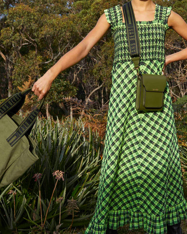 Sans Beast Khaki Bandolier boxy style crossbody bag and Khaki Overflow Tote bag worn with a black and green check dress.