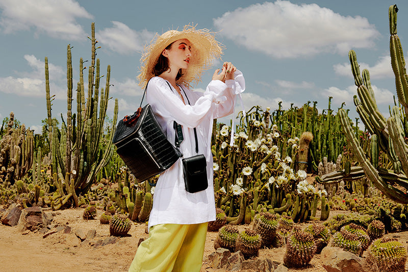 Juliette in the cactus fields, with the Call Me Phone Sling + Liaison Backpack.