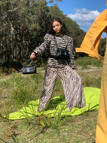 Crystal wears a zebra printed outfit and carries two black handbags, the Salon and Lobby crossbody bags.  She is standing outside against a backdrop of the Australian bush.