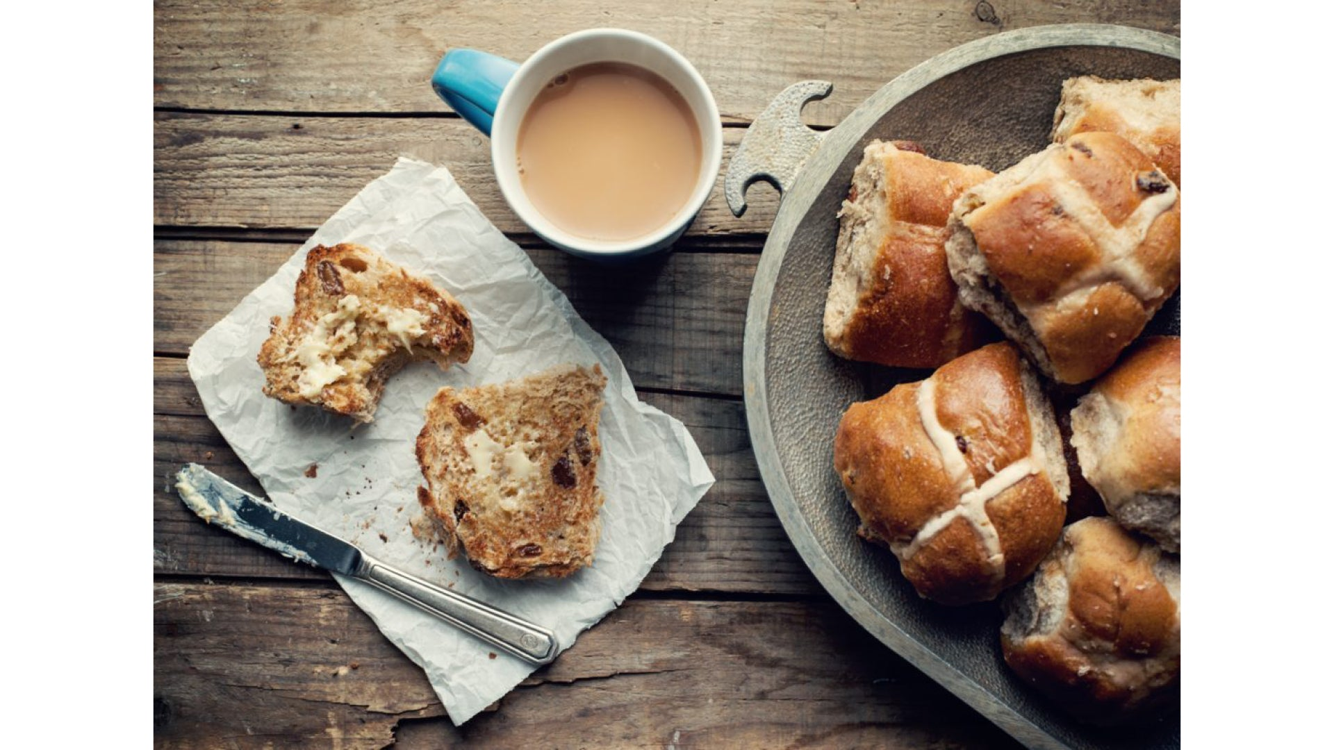 Image of hot cross buns on a wooden table. One has been buttered, with a knife placed beside it. A cup of tea sits next to it.