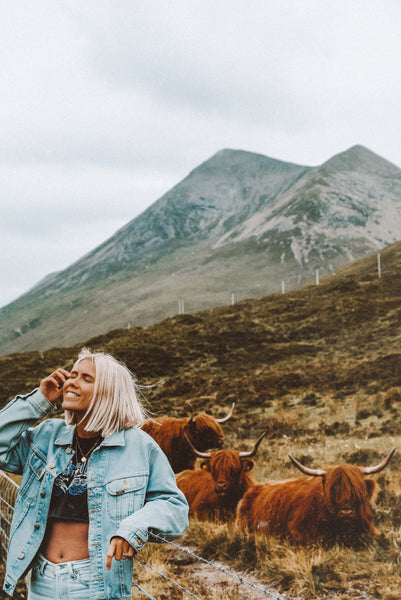 Karissa in the Scottish Highlands, standing near a group of cows
