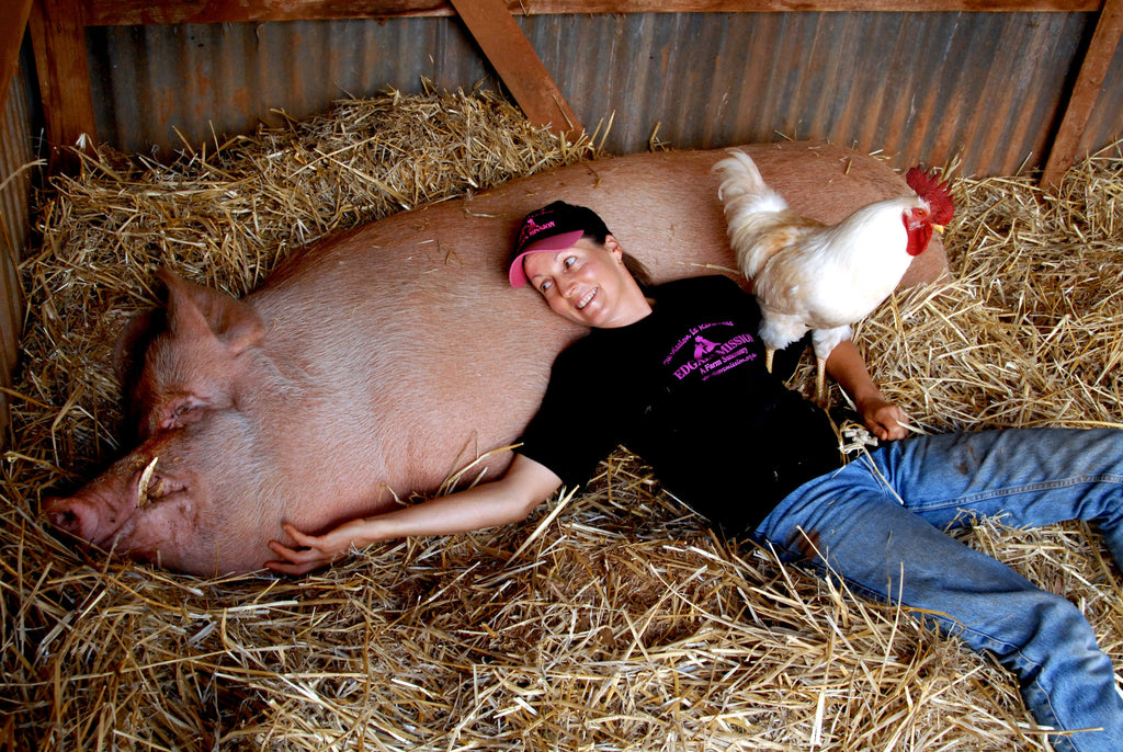 Pam Ahern at Edgars Mission, lying on straw next to a very large pig.