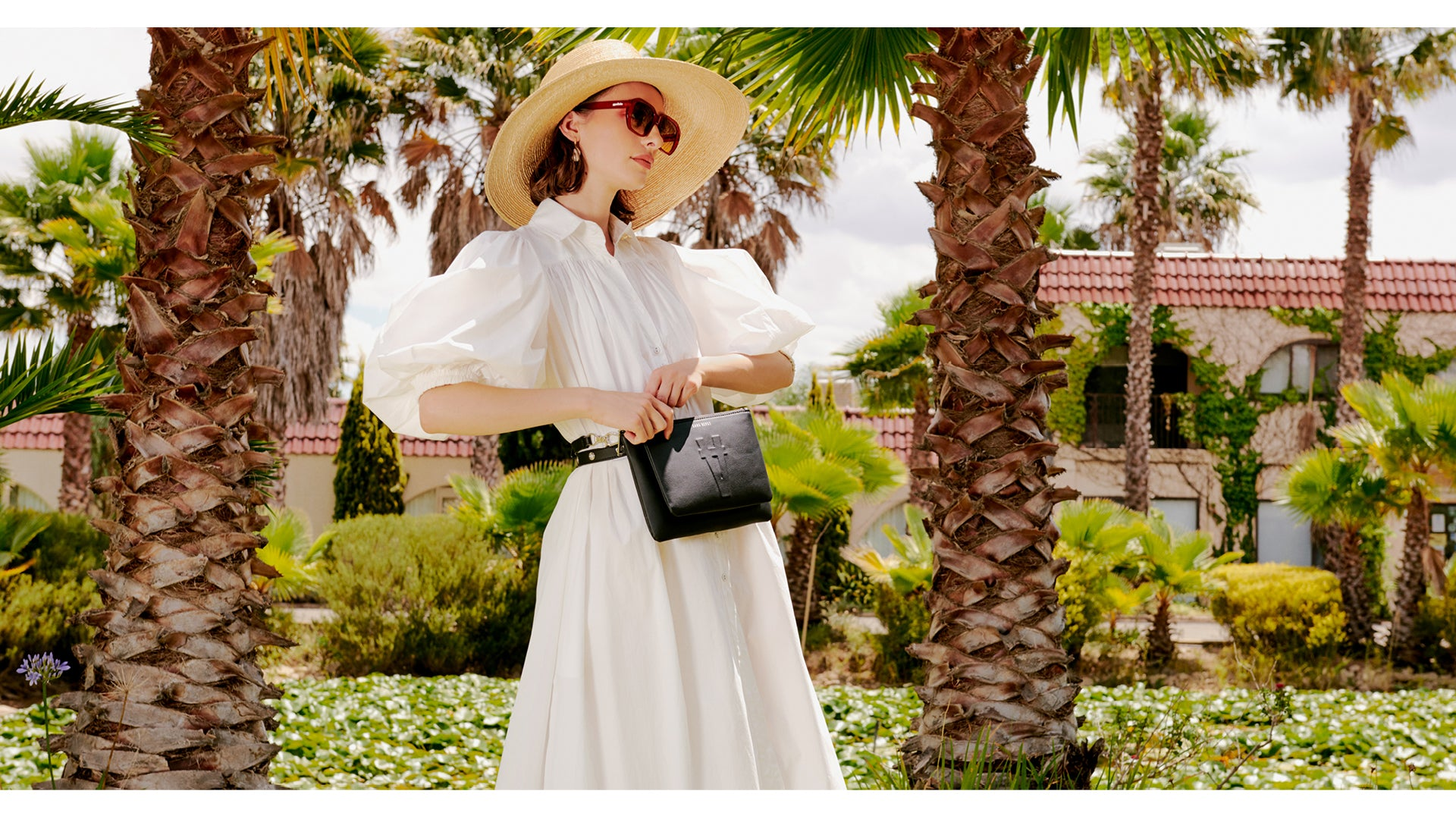 Juliette in a white dress + sun hat, holding The Francisco Double Pouch in Noir Cactus.