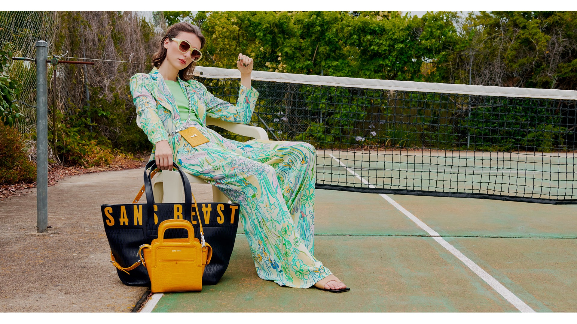 Juliette on a tennis court in a floral pantsuit, with The Activist Tote in Midnight Pebble + The Long Lunch Tote in Mustard Croco.