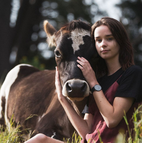 An image of Emma Hakansson snuggled next to a beautiful cow and touching it's face.