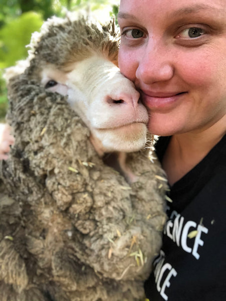 Joanne Lee pictured cuddled up to a sheep.