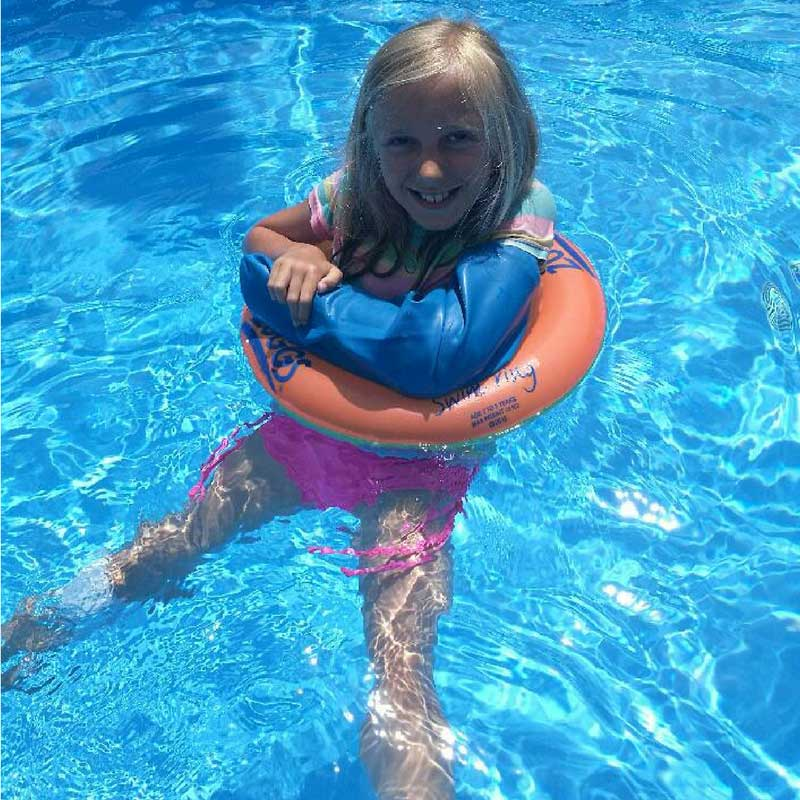Allegra wearing her Bloccs Waterproof arm cast protector in a swimming pool