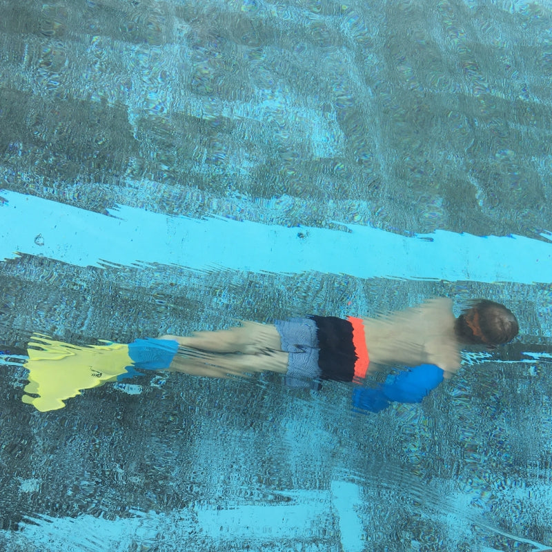 Beth's son swimming underwater with his waterproof full arm cover
