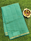 Semi raw silk saree teal blue with half diamond zari border and self embose pattern
