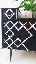 Close up of diamond geometric pink design on black on dresser drawers