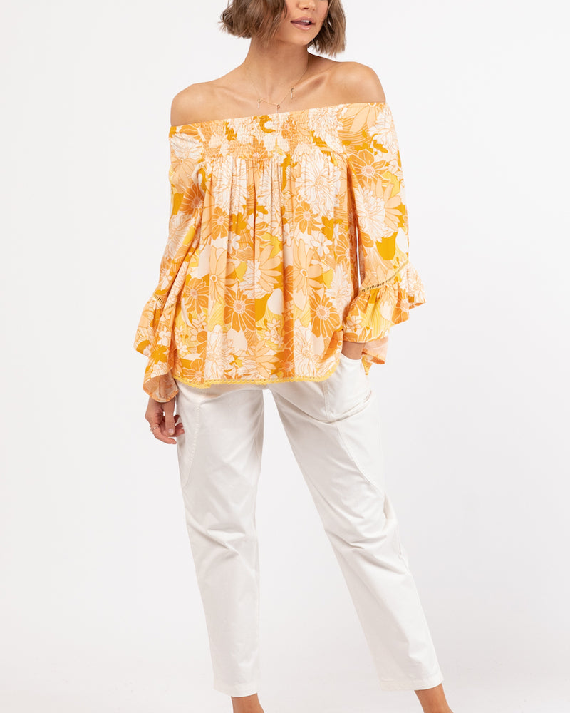 shirred off the shoulder printed top with long ruffled sleeves and loose fitting body.