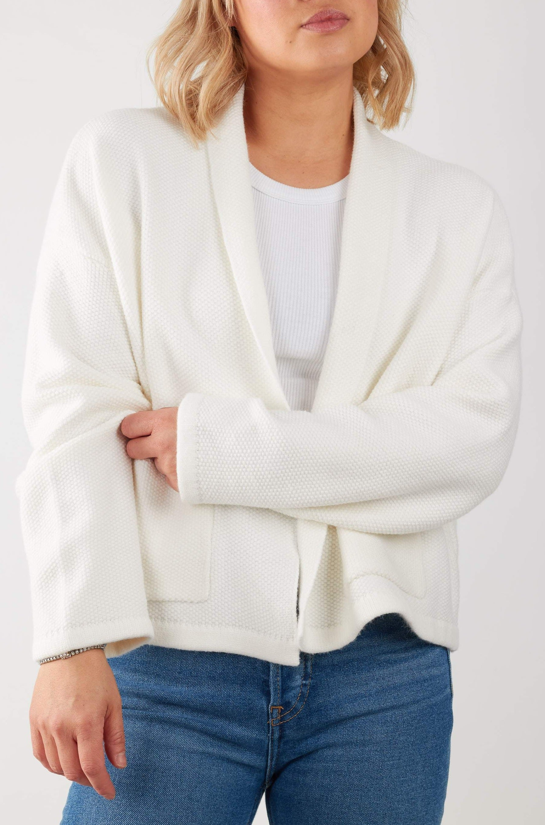 Shawl collar  open front cardigan with patch pockets in a soft waffle knit. Slightly cropped boxy fit.