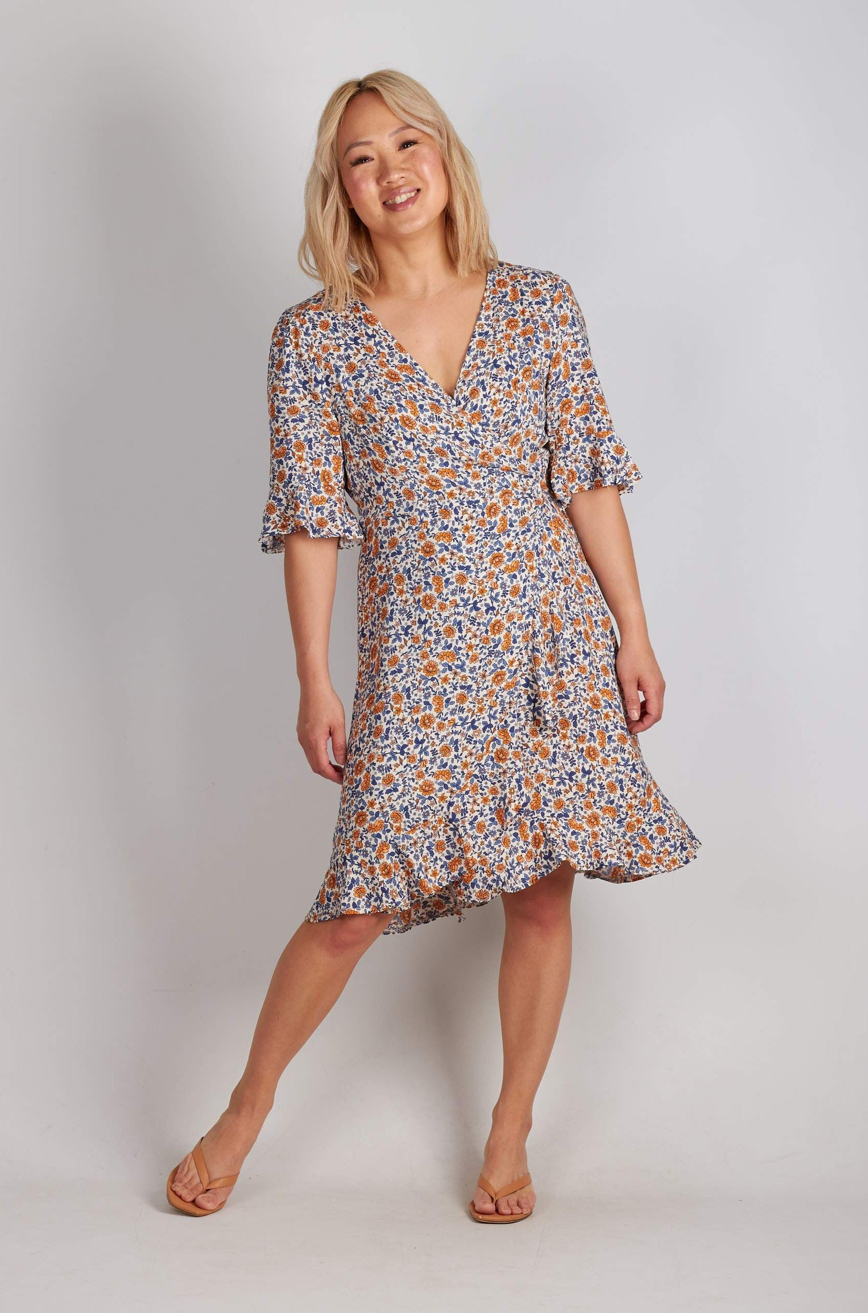 White & blue ditzy floral wrap mini dress with ruffle hem and short sleeves.
