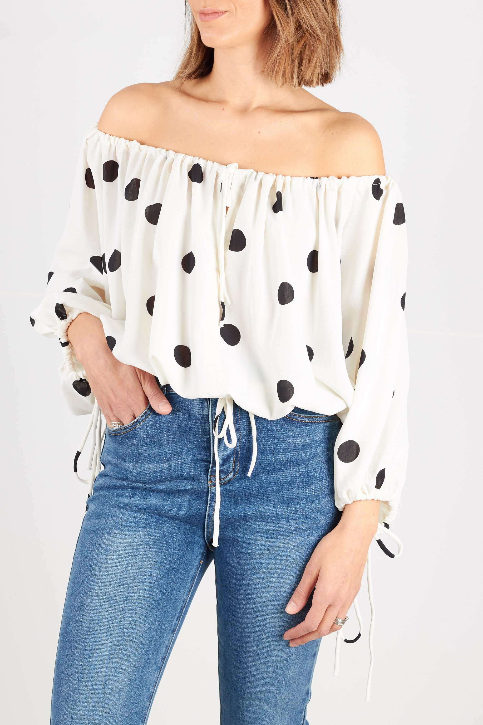 White blouse with large black spots with drawstring neckline, balloon sleeve cuffs  and hem. Also available in black with white spots.
