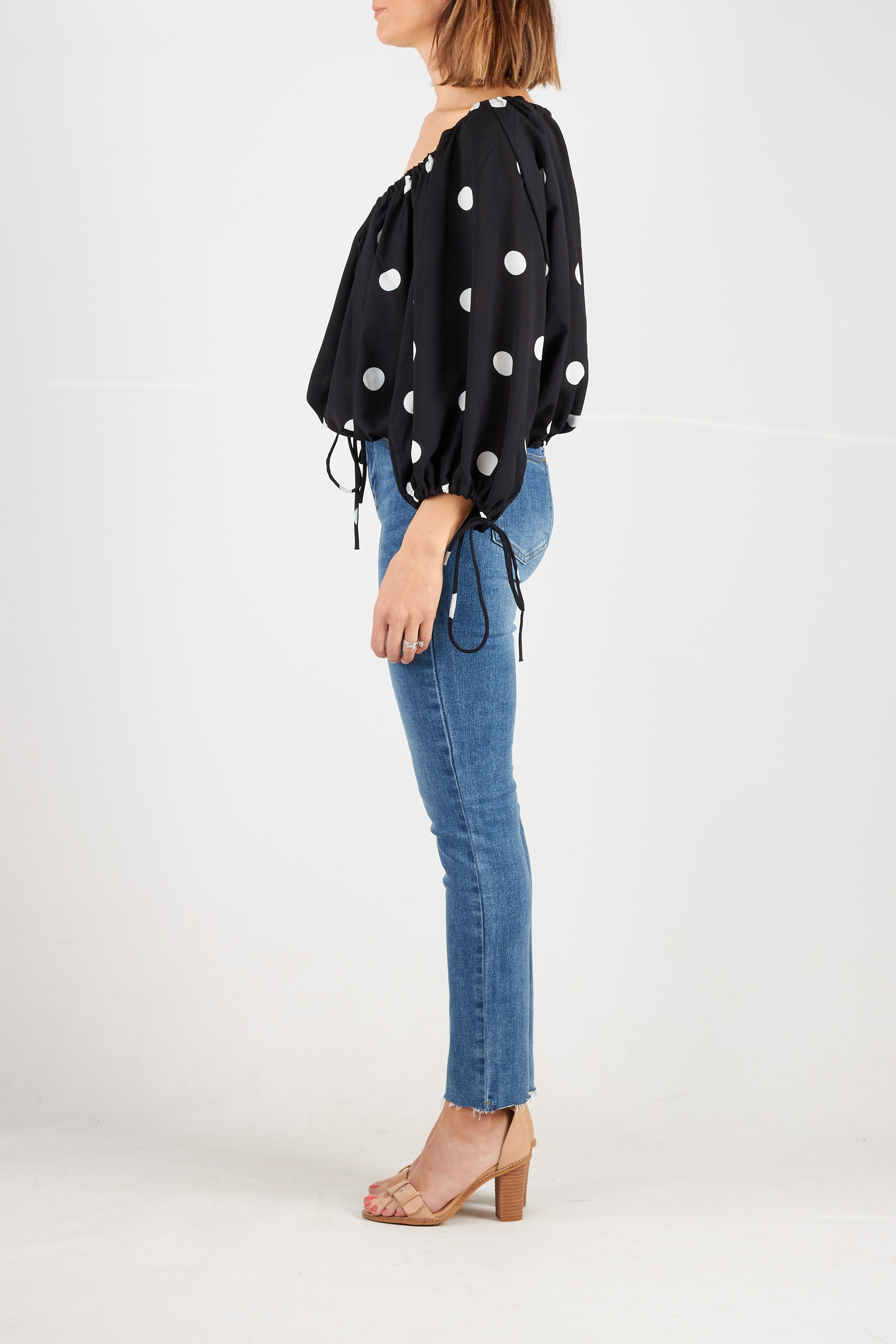 Black blouse with large white spots with drawstring neckline, balloon sleeve cuffs  and hem. Also available in white with black spots.