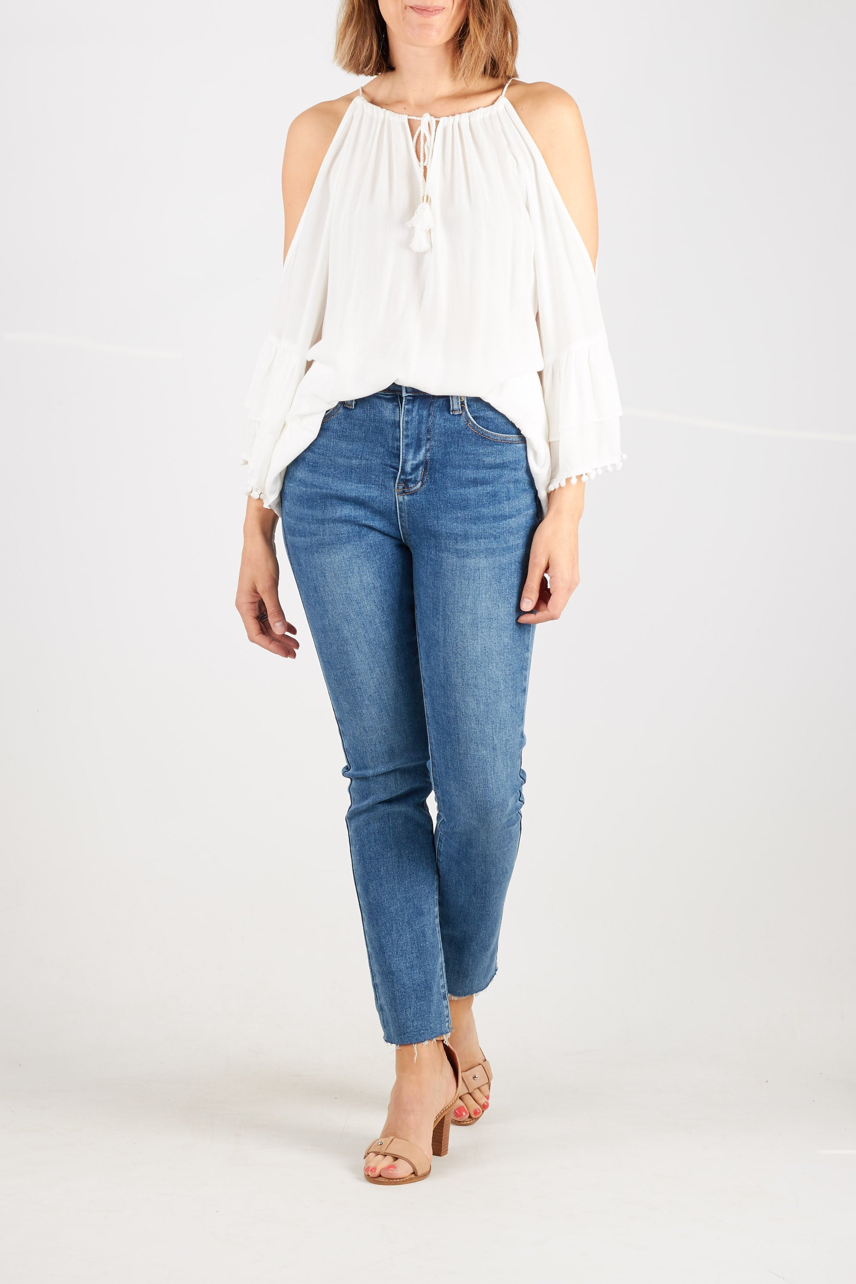 White blouse with cutaway shoulders, rope tie at neck and pom pom tassel detailing on sleeves and hem.