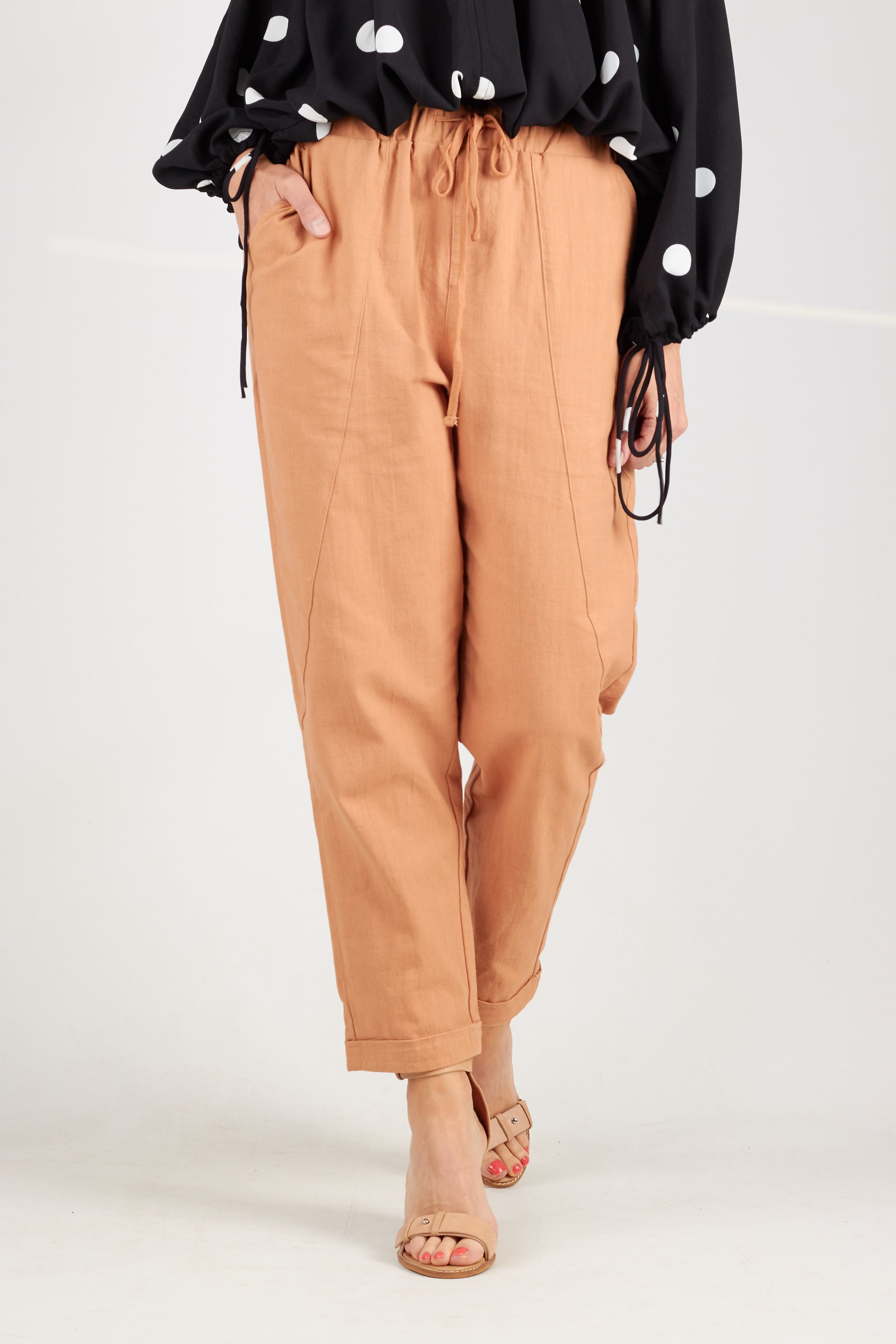 Tan coloured cotton pants with elasticised drawstring waistband and side pockets. Tapered leg with cuffed hem that falls at ankle length.
