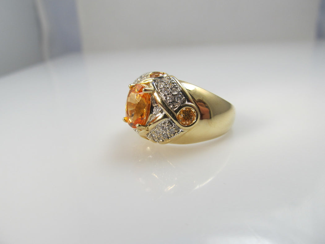 Modern estate 14k gold ring with a 2.50ct center orange sapphire and diamonds
