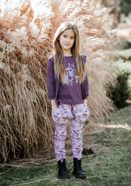 cool girl wearing purple aster and oak organic cotton fairy garden long sleeve tee cardigan and pants with black lace-up boots in garden