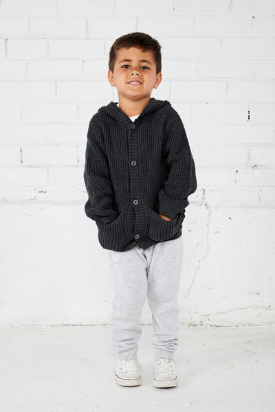 young boy wearing miann and co cotton knit pants in grey and waffle knit hoodie cardigan in charcol autumn and winter boys clothing