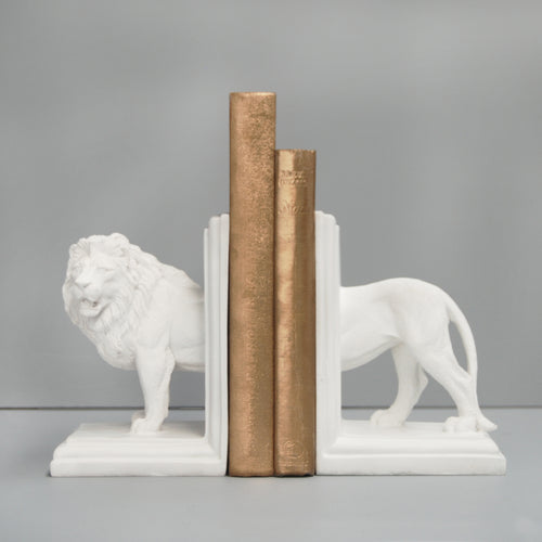 set of white lion bookends holding gold books on a grey and white background white moose australia