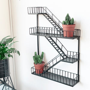 new york style fire escape metal shelf displayed with two cacti succulents in pots