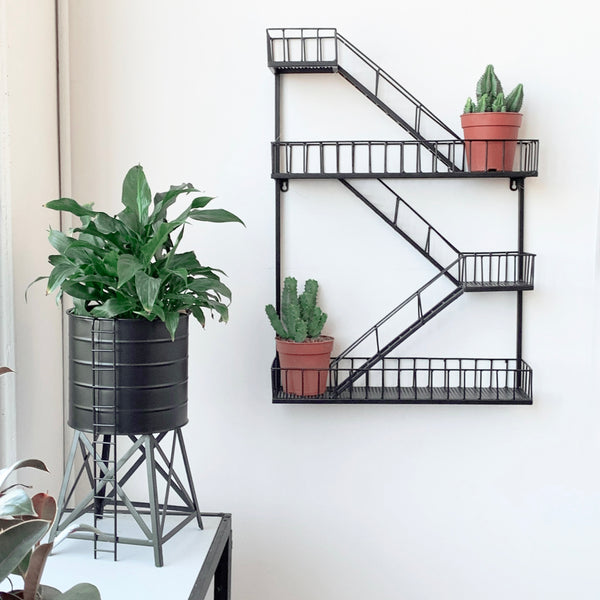 metal water tower pot with lush green plant and new york fire escape shelf on wall with cacti succulents crazy plant lady gift ideas