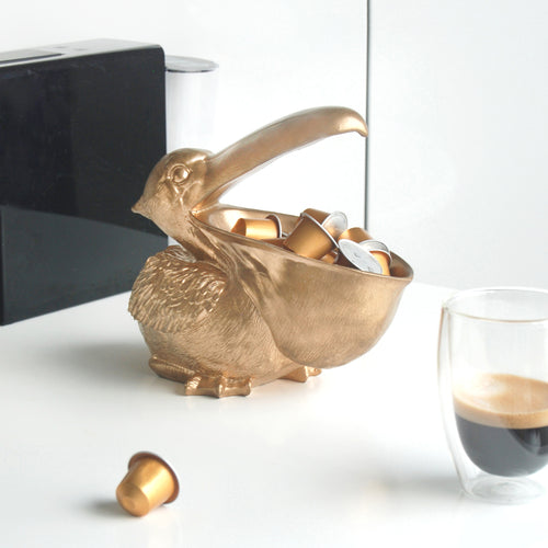 gold pelican bowl holding gold coffee pods in its mouth sitting next to a cup of coffee on a white kitchen bench